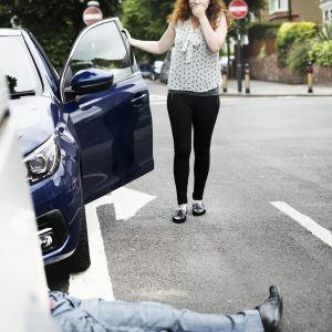 Person lying on the ground after a car accident